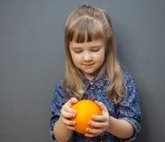 微笑的小女孩用大桔子 库存照片