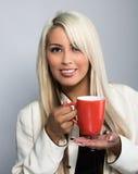 微笑的小姐,当享用她温暖的咖啡时 免版税库存图片