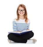 微笑的小学生女孩坐地板 免版税库存照片