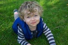 微笑的小孩在庭院里 免版税库存图片