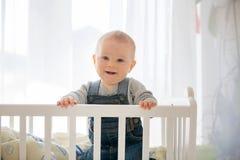 微笑的小孩男孩,使用与在小儿床的小的兔子玩具 免版税图库摄影