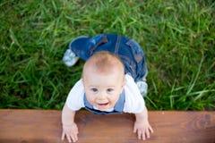 微笑的小孩男孩,使用与在开花的春天庭院的玩具 库存图片