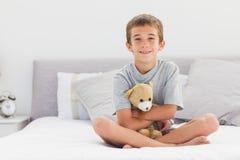 微笑的小男孩坐拿着他的玩具熊的床 库存照片