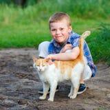 微笑的小男孩富感情地拥抱一只红色猫 室外 免版税库存照片