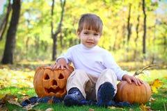 微笑的小男孩用二个万圣节南瓜 库存照片