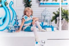 微笑的小白肤金发的甜女孩坐白色圣诞节球和圣诞树围拢的游廊 库存照片