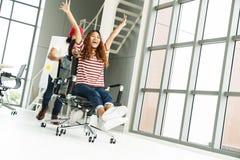 微笑的小组不同种族的年轻创造性的配合获得乐趣笑和在办公室主持推挤 庆祝为su的工友 免版税库存照片