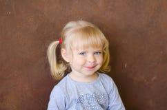 微笑的小滑稽的白肤金发的女孩画象  库存照片