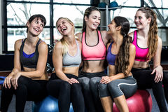 微笑的小组适合妇女,当坐锻炼球时 免版税库存照片