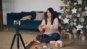 微笑的少女vlogger记录关于礼品包装材料教的订户的录影装饰当前箱子与 股票录像