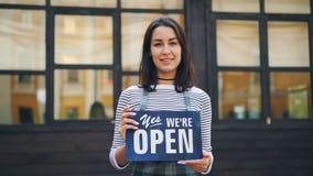 微笑的少妇企业家藏品慢动作画象我们是站立户外在她前面的开放标志新 股票录像