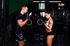 微笑的少妇和个人教练员在健身房行使 免版税库存图片