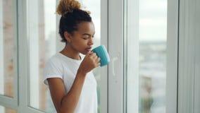 微笑的少妇喝看起来的茶站立在窗口附近和外部在家享受业余时间 影视素材