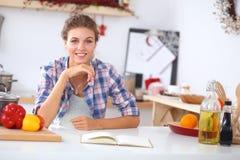 微笑的少妇在厨房里,被隔绝  图库摄影