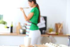 微笑的少妇在厨房里,被隔绝  库存照片
