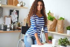 微笑的少妇在厨房里,被隔绝  免版税库存图片