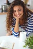 微笑的少妇在厨房里,  免版税库存照片