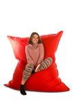 微笑的少妇坐居住的红色装豆子小布袋沙发椅子 免版税图库摄影