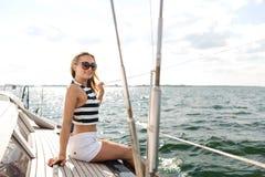 微笑的少妇坐游艇甲板 免版税库存图片