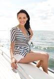 微笑的少妇坐游艇甲板 库存照片