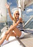 微笑的少妇坐游艇甲板 图库摄影