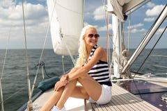微笑的少妇坐游艇甲板 免版税库存照片