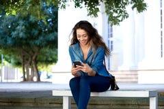 微笑的少妇坐长凳使用手机 免版税库存照片