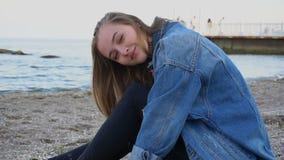 微笑的少妇基于海滩并且摆在秘密审议,坐与贝壳的沙滩在温暖的春天晚上 股票视频
