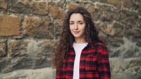 微笑的少妇慢动作画象有长的卷发佩带的白色T恤杉和明亮的衬衣身分的 股票视频