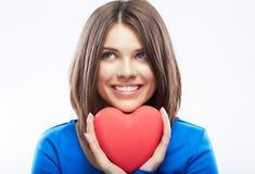 微笑的少妇拿着红色心脏,情人节标志 女孩 免版税图库摄影