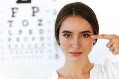 微笑的少妇特写镜头在视觉眼睛测试板前面的 免版税库存图片