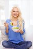 微笑的少妇用蔬菜沙拉在家 免版税库存图片