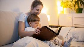 微笑的少妇读书故事被定调子的画象对她的小孩儿子的在去前睡 库存照片