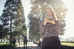 微笑的少妇谈话在她的在街道上的智能手机 沟通与朋友,释放电话和消息青年人的 图库摄影