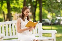 微笑的少妇阅读书在夏天停放 库存照片