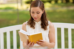 微笑的少妇阅读书在夏天停放 库存图片