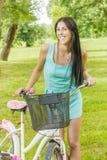 微笑的少妇画象有自行车的在公园 免版税库存图片