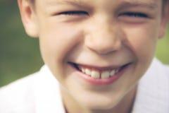 微笑的少年男孩背景的被弄脏的defocusing的图片  免版税图库摄影