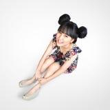 微笑的少年亚裔女孩坐地板 免版税图库摄影
