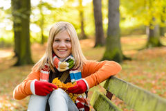 微笑的少年女孩坐的秋天公园长椅 免版税库存图片