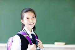微笑的少年学生女孩在教室 免版税库存照片