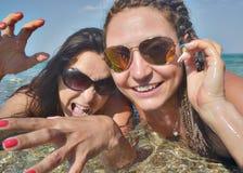 微笑的尖叫的女性面对海太阳镜 免版税库存图片