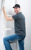 微笑的工作者人拿着在白色背景的一架梯子 免版税库存图片