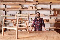 微笑的工匠在他的有木椅子框架的木制品演播室 免版税库存照片