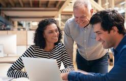 微笑的工友一起谈话在一台膝上型计算机在办公室 免版税库存照片