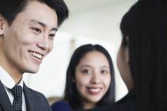 微笑的工友谈话在办公室 免版税库存照片