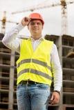 微笑的工程师画象摆在反对工作的安全帽的c 库存照片