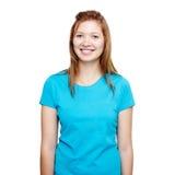 微笑的常设妇女年轻人 蓝色T恤杉设计观念 免版税图库摄影
