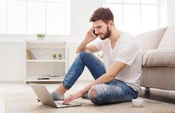 微笑的年轻人在家有膝上型计算机和机动性的 免版税库存照片