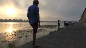 微笑的年轻人在河岸走在精采日落在Slo Mo 股票视频